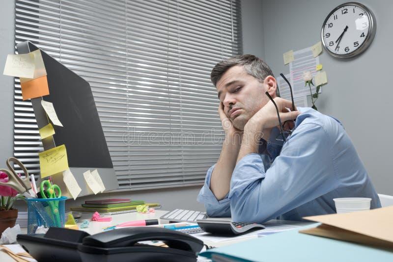Deprimerad kontorsarbetare på hans skrivbord arkivfoton