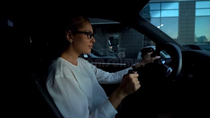 Deprimerad kvinna som dricker vin, medan köra bilen, risk av den farliga turen för olycka fotografering för bildbyråer
