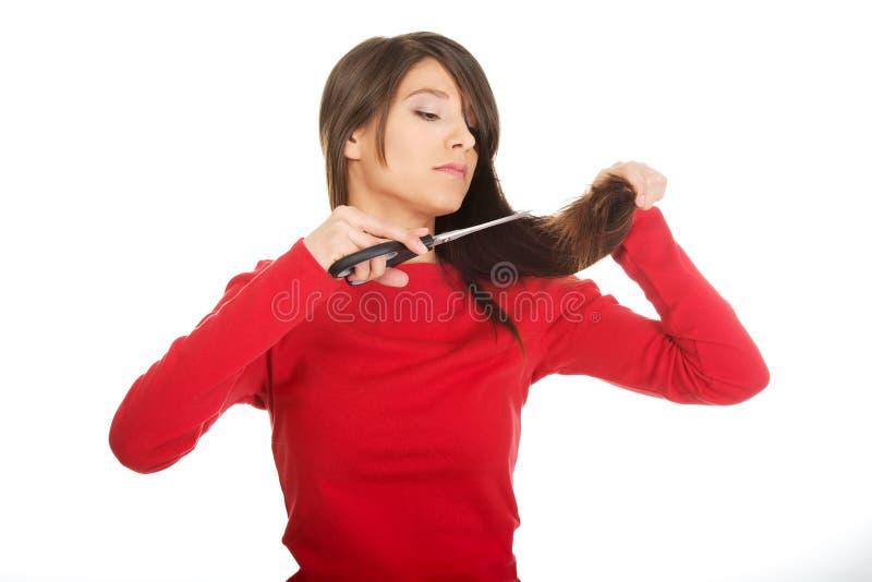 Deprimerad kvinna som klipper hennes hår arkivfoto
