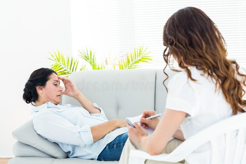 Deprimerad kvinna som ligger på soffan medan hennes terapeut som tar anmärkningar royaltyfri bild