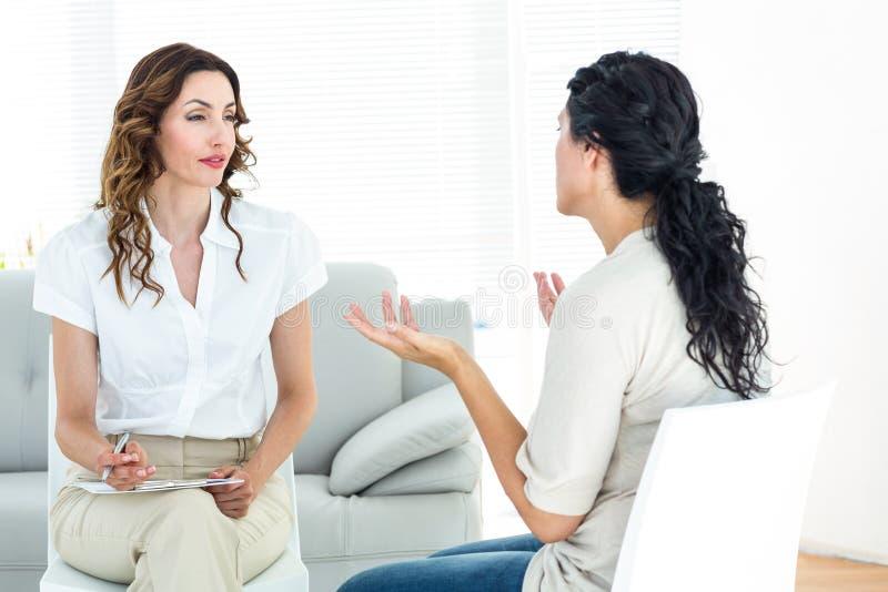 Deprimerad kvinna som talar till hennes terapeut royaltyfri bild