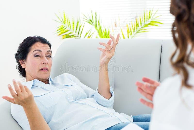 Deprimerad kvinna som talar till hennes terapeut royaltyfri foto
