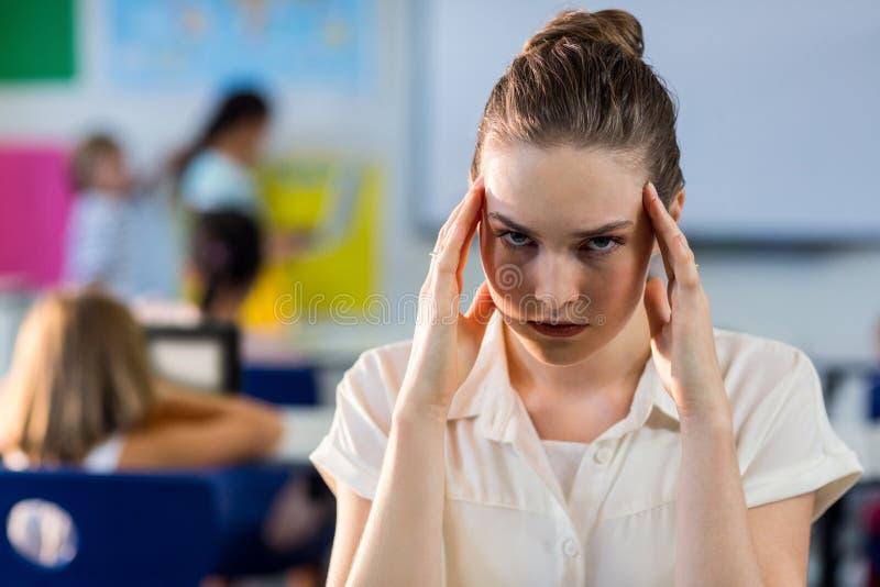 Deprimerad lärarinna som trycker på hennes huvud arkivbild