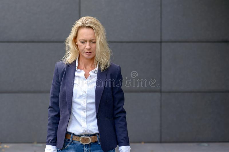 Deprimerad ledsen blond kvinna i ett stilfullt omslag arkivfoton