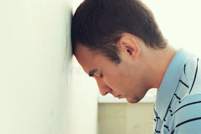 Deprimerad man hans huvud mot en vägg grabbs dängande hans huvud mot väggen Borra grabben in i fördjupning arkivfoto