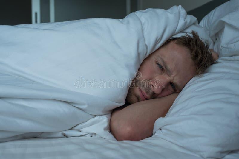 Deprimerad man som ligger i hans dåliga säng och känsla royaltyfri bild