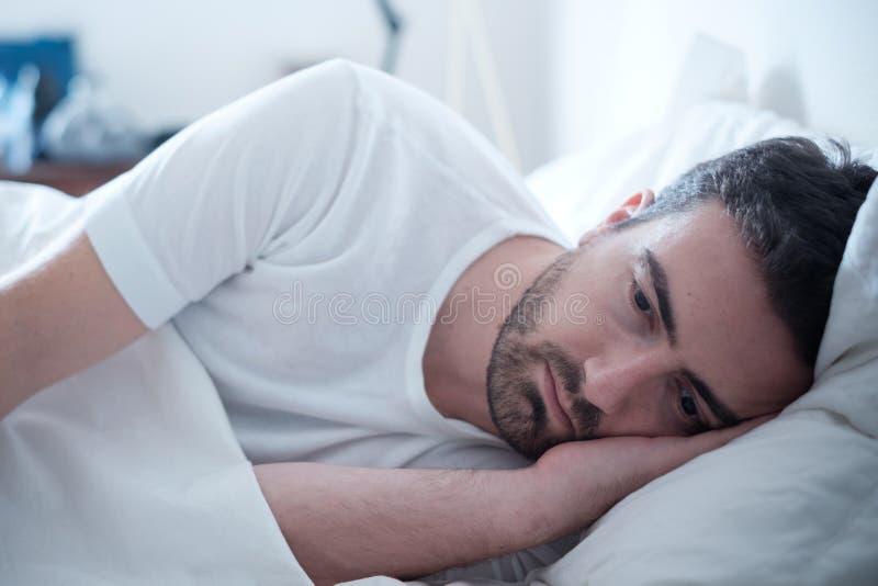 Deprimerad man som ligger i hans dåliga säng och känsla arkivbilder