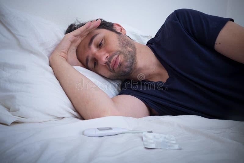 Deprimerad man som ligger i hans säng royaltyfri bild