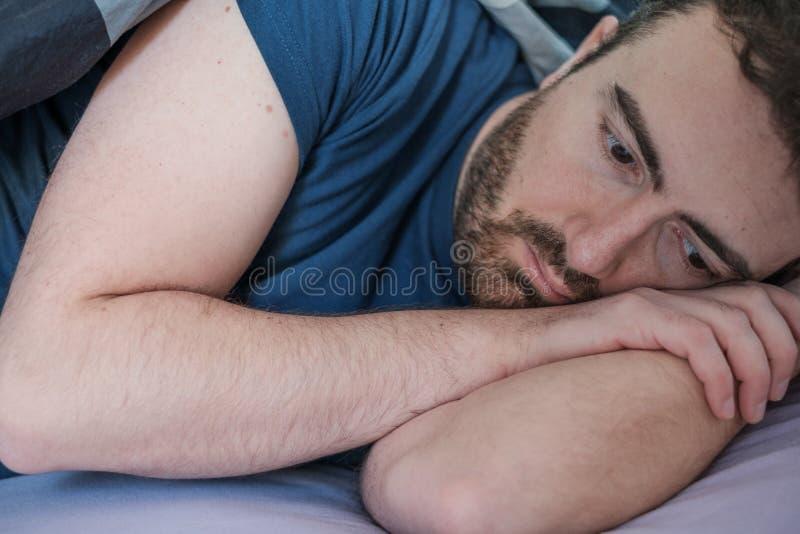 Deprimerad man som ligger i hans säng arkivbild