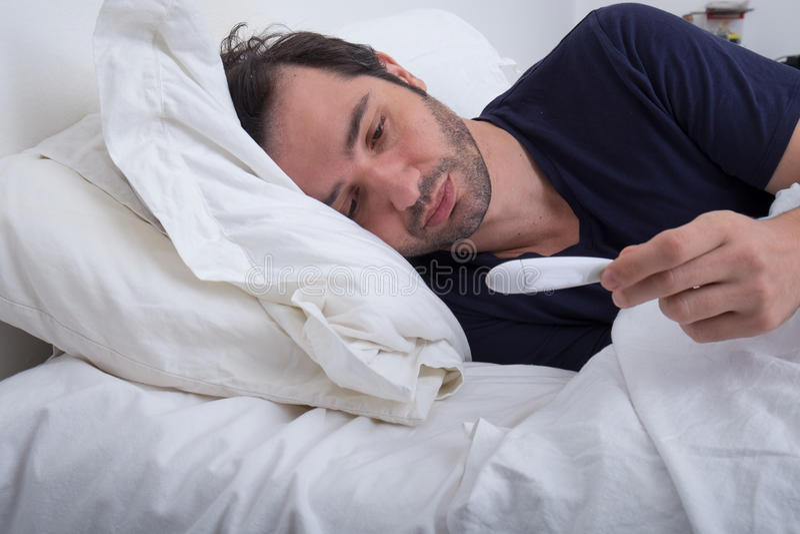 Deprimerad man som ligger i hans säng arkivfoto