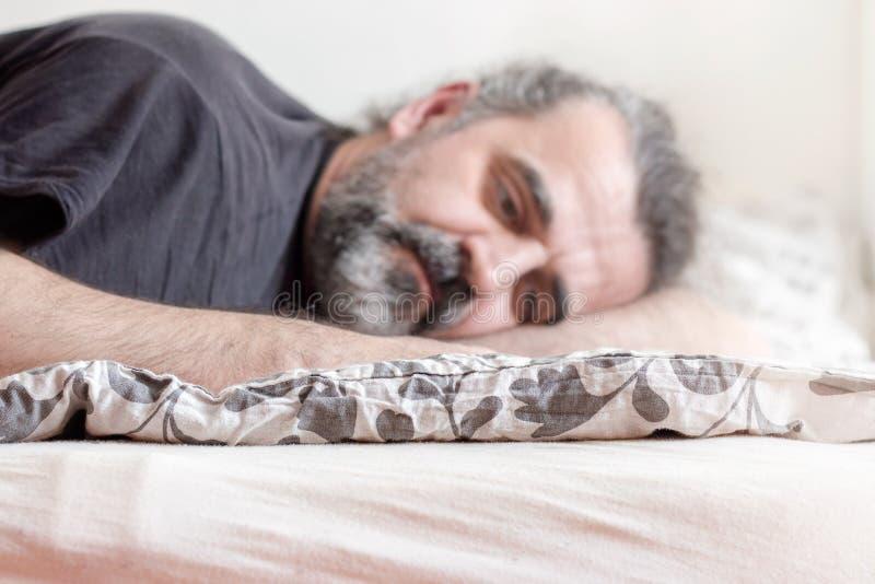 Deprimerad man som ligger i säng fotografering för bildbyråer