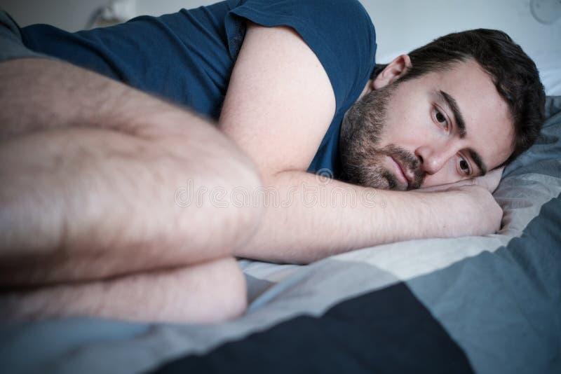 Deprimerad man som ligger i säng som känner sig dålig royaltyfria bilder