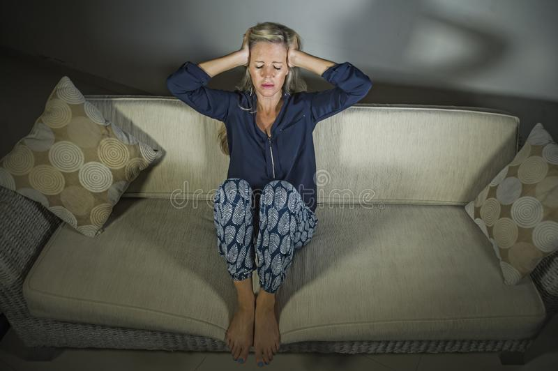 deprimerad och angelägen härlig blond för för kvinnalidandefördjupning och huvudvärk känsla frustrerad sittande hemmastadd för so arkivfoto