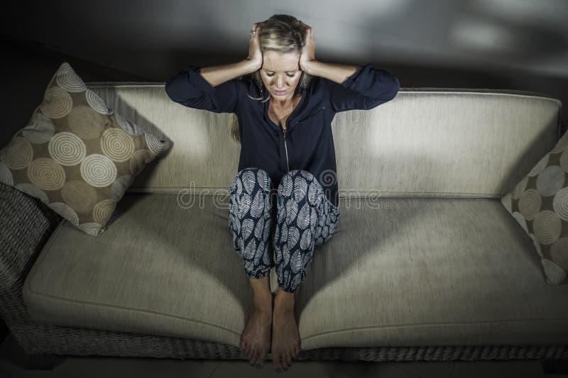 deprimerad och angelägen härlig blond för för kvinnalidandefördjupning och huvudvärk känsla frustrerad sittande hemmastadd för so royaltyfri foto