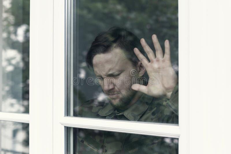 Deprimerad och trött soldat med krigsyndrom och våldproblem royaltyfri fotografi