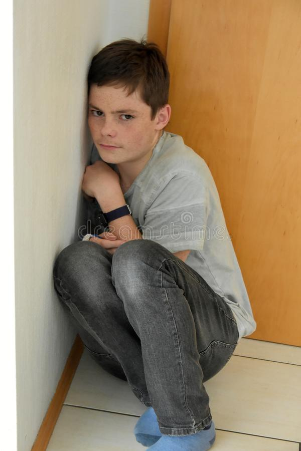 Deprimerad pojke som döljas i hörnet av ett rum royaltyfria bilder