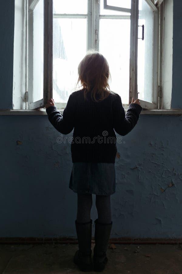 Deprimerad pootflicka som står det near fönstret fotografering för bildbyråer