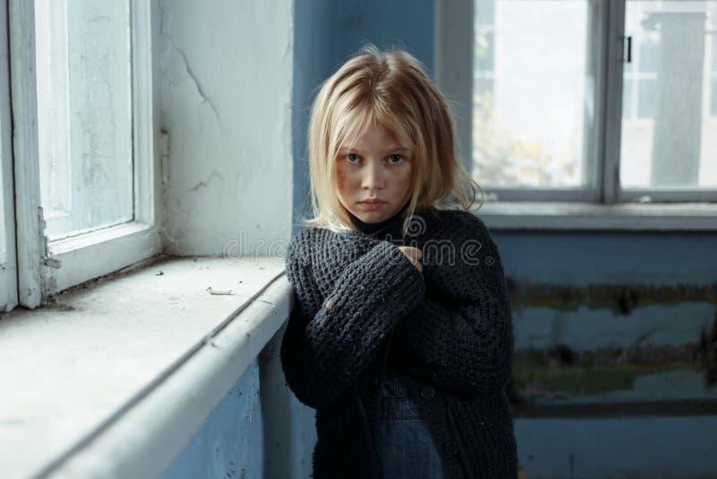 Deprimerad pootflicka som står det near fönstret arkivbild