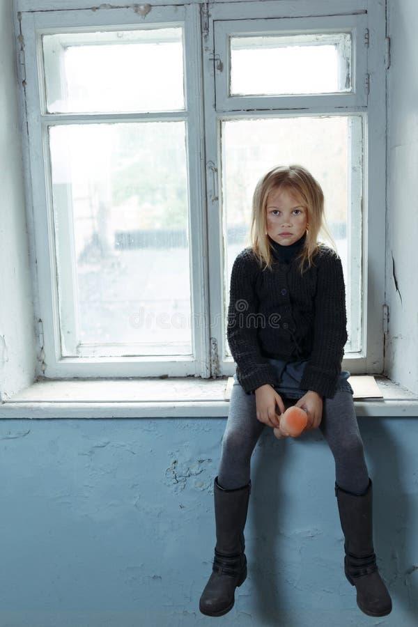Deprimerad pootflicka som står det near fönstret royaltyfria foton
