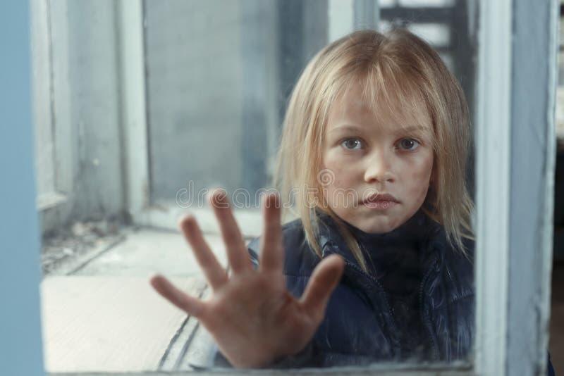 Deprimerad pootflicka som står det near fönstret royaltyfri bild