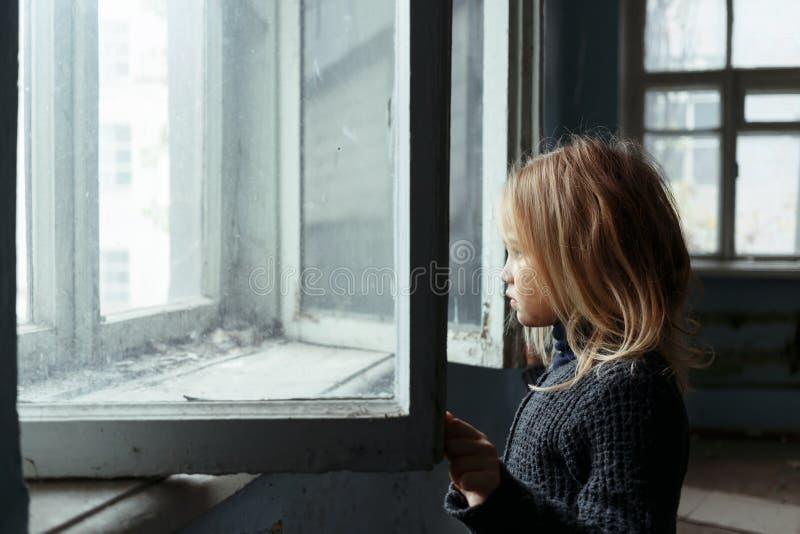 Deprimerad pootflicka som står det near fönstret royaltyfri foto