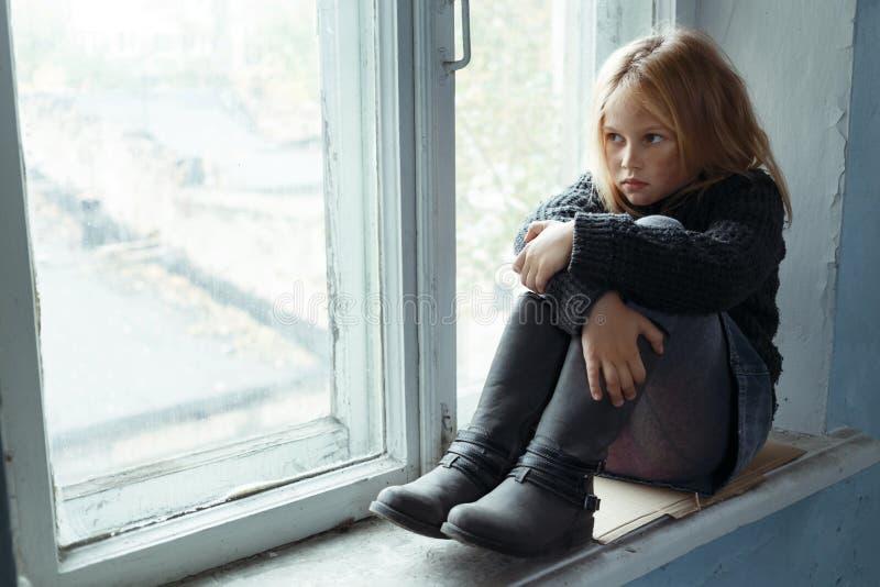 Deprimerad pootflicka som står det near fönstret arkivbilder