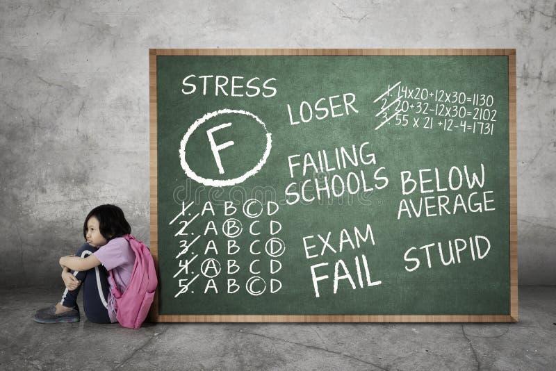 Deprimerad skolflicka med hennes missade examenställning royaltyfri bild
