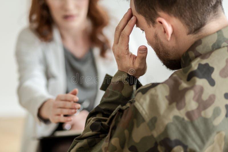 Deprimerad soldat med självmords- tankar som bär den gröna likformign under terapi med psykiatern arkivbild