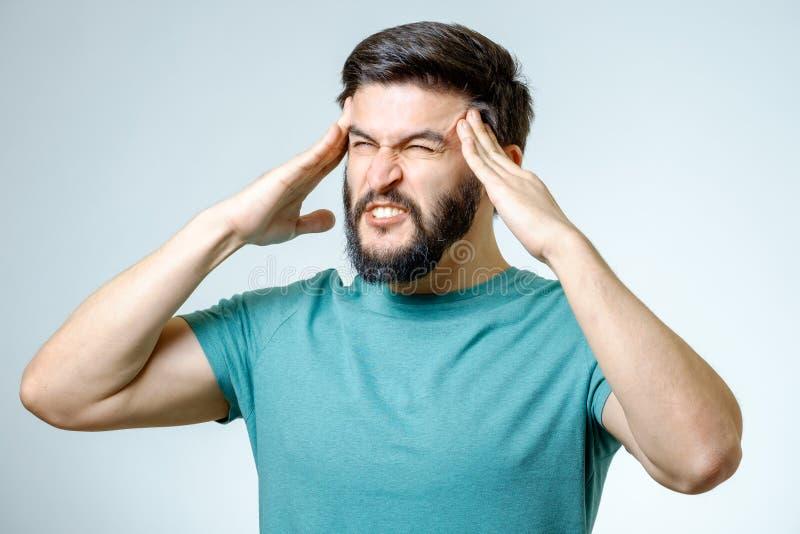 Deprimerad stilig skäggig man som trycker på ha en huvudvärk royaltyfria foton