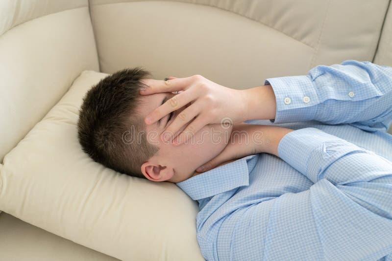 Deprimerad tonåring som ligger på soffan som täcker hans framsida med hans händer royaltyfria foton