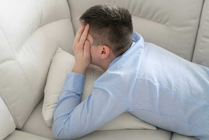 Deprimerad ton?ring som ligger p? soffan som t?cker hans framsida med hans h?nder arkivfoton