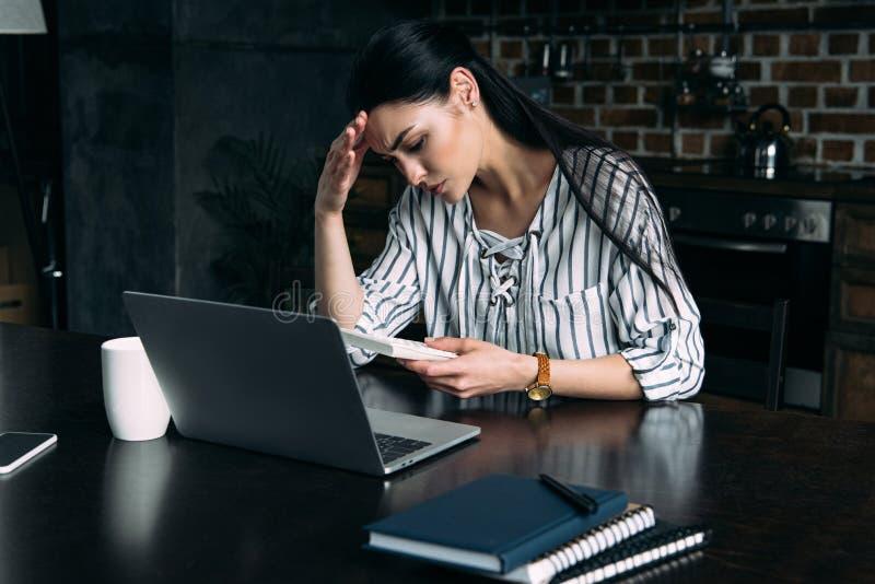 deprimerad ung kvinna med räknemaskinen och bärbara datorn som hemma räknar skatt royaltyfri foto