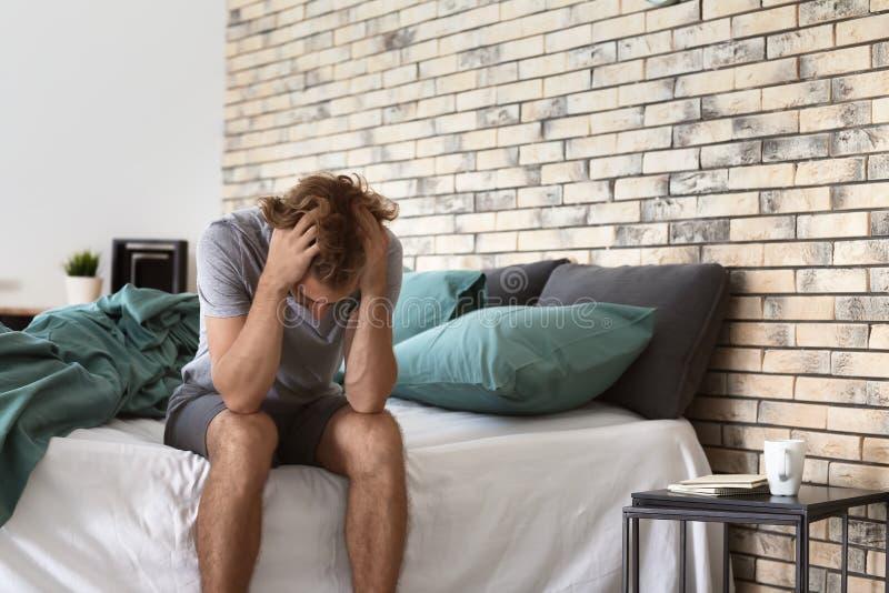 Deprimerad ung man som sitter på säng royaltyfria foton