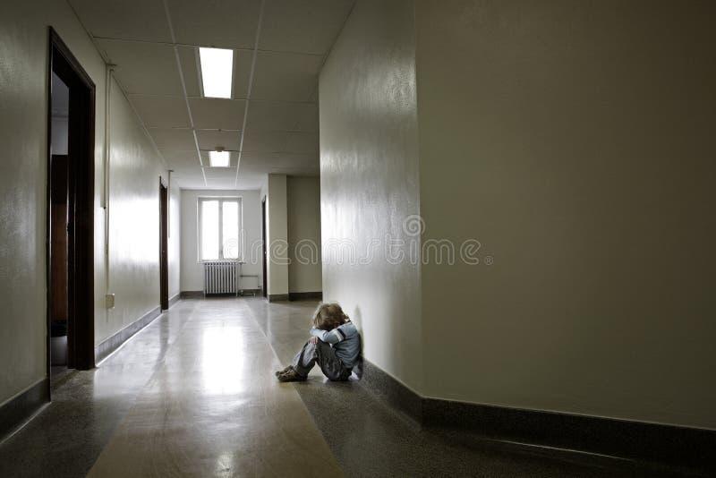 Deprimerad ung pojke som bara sitter i ett hall royaltyfri bild