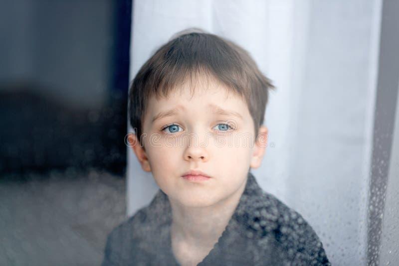Deprimerade 7 år pojkebarn som ut ser fönstret royaltyfri foto