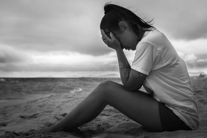 Deprimerade ledsna kvinnor som sitter med hennes händer på hennes framsida svart white arkivbild