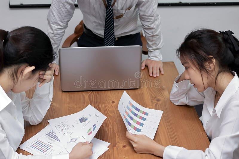 Deprimerade stressade unga asiatiska affärskvinnor som lider från strängt problem mellan mötet i konferensrum royaltyfri foto