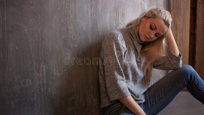 Deprimerande flicka Sitter på golvet Fördjupning och kronisk trötthet Ung härlig blondin i grå tröja och jeans royaltyfria foton