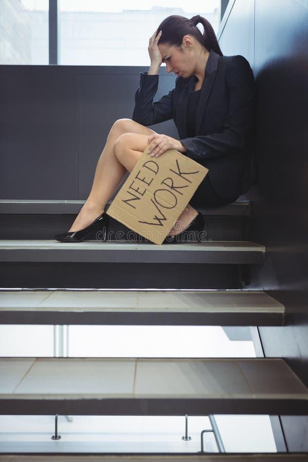Deprimerat affärskvinnasammanträde på trappa som rymmer papparket med textbehovsarbete royaltyfria foton