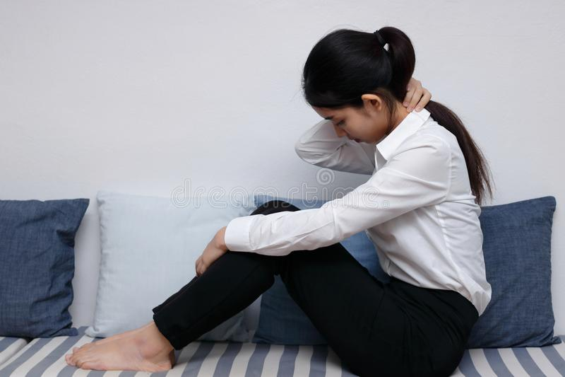 Deprimerat ensamt ungt asiatiskt kvinnasammanträde i soffa i vardagsrum royaltyfri bild