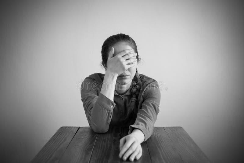 Deprimerat kvinnasammanträde på en tabell arkivbild