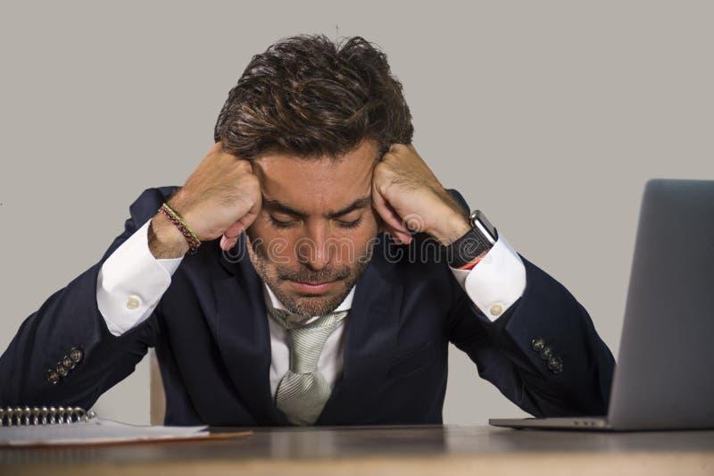 Deprimerat och förkrossat arbete för stressad affärsmankänsla på skrivbordet för kontorsdator som tröttas och evakueras besegrat  arkivbilder