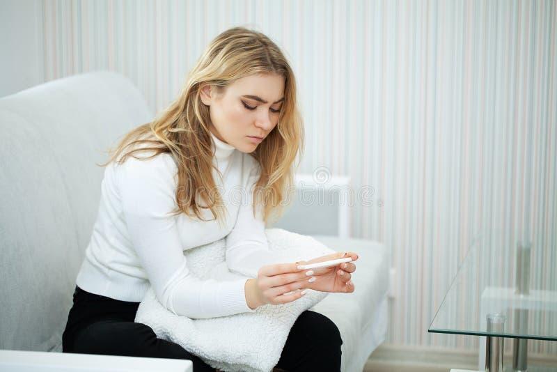 Deprimerat och ledset a för positiv för graviditetstest känsla för ung kvinna arkivbilder