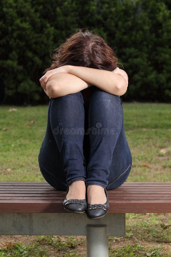 Deprimerat och sorgsenhet för tonåring ensamt i en parkera fotografering för bildbyråer