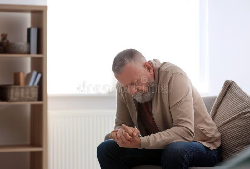 Deprimerat sammanträde för hög man på soffan royaltyfri foto