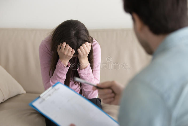 Deprimerat skriande kvinnasammanträde med hennes huvud ner, psykolog royaltyfri bild