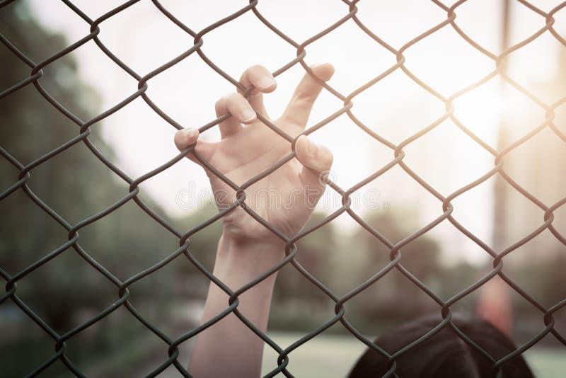 Deprimido, problema, ajuda e possibilidade A mão impossível do aumento das mulheres na cerca do elo de corrente pede a ajuda imagens de stock royalty free