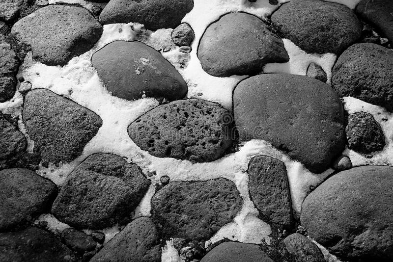 Deprimierender Schwarzweiss-Hintergrund von Kopfsteinen und von Schnee lizenzfreie stockfotografie