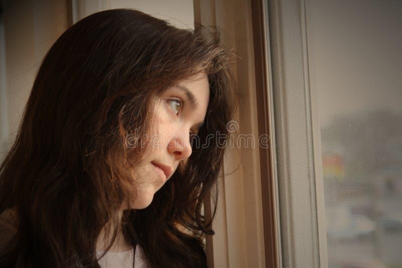 Deprimiert, Fenster heraus schauend stockfoto