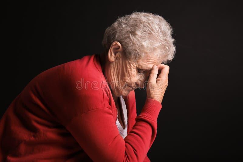 Deprimierte ältere Frau auf dunklem Hintergrund stockfotografie